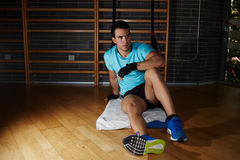 Handsome athlete with lifting glows seated on fitness mat. Having a rest after workout Royalty Free Stock Images