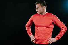 Handsome athlete man in red sportswear standing over dark background, thinking over problems in his life, holding hands on his wai. Caucasian sportsman wearing Royalty Free Stock Images