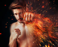 Handsome athlete punching with flame around his arm Stock Photography