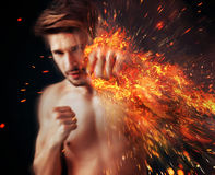 Handsome athlete punching with flame around his fist Royalty Free Stock Images