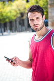 Handsome athlete sending a text Royalty Free Stock Photos