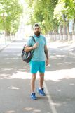Handsome athlete. Sport coach with backpack ready for workout outdoors. Sport is way of life. Guy handsome bearded face. In sport uniform in park. Summer stock image