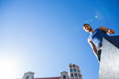 Handsome athlete standing on column against blue sky Stock Photo