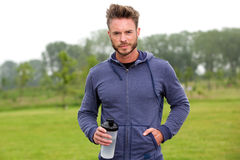 Handsome athlete standing outside in park with water bottle Royalty Free Stock Photography