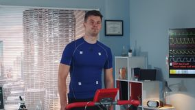 Handsome athlete walking on treadmill with electrodes connected on him. In scientific sports laboratory stock footage
