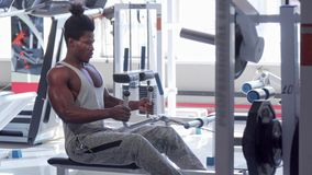 Handsome athletic African man exercising on seated low row machine at gym. Ripped muscular sportsman working out at sports studio. Strong sportsman doing back stock video