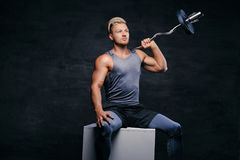 Handsome, athletic blond male holds barbell on his shoulder. Portrait of a handsome, athletic blond male sits on a white box and holds barbell on his shoulder Royalty Free Stock Image