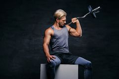Handsome, athletic blond male holds barbell on his shoulder. Portrait of a handsome, athletic blond male sits on a white box and holds barbell on his shoulder Royalty Free Stock Photo