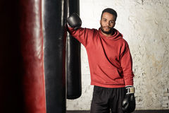 Handsome athletic dark-skinned guy in a red sweatshirt leaning on a black punching bag in a gym. Royalty Free Stock Images