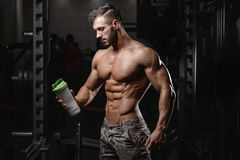 Handsome athletic fitness man holding a shaker and posing gym. On diet royalty free stock images