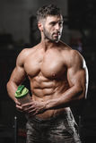 Handsome athletic fitness man holding a shaker and posing gym Royalty Free Stock Image