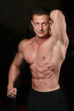 Handsome athletic fitness man posing and trains in the gym Royalty Free Stock Photography