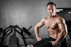 Handsome athletic fitness man posing and trains in the gym Stock Photo