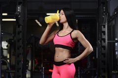 Handsome athletic fitness woman holding a shaker and posing royalty free stock photos