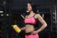 Handsome athletic fitness woman holding a shaker and posing. Fitness strength training workout bodybuilding concept background - muscular bodybuilder sexy woman Stock Image