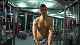 Handsome athletic guy doing pectorals on the crossover trainer in the gym. front view. Fitness model stock video