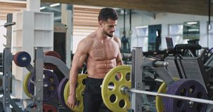 A handsome athletic guy is putting weights on a weight bar, he has tattoos on his chest and body. 4k stock video footage
