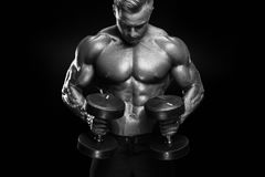 Handsome athletic guy workout with dumbbells Royalty Free Stock Photos