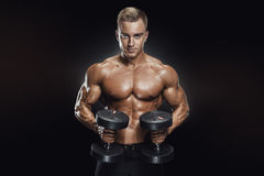 Handsome athletic guy workout with dumbbells Royalty Free Stock Photography