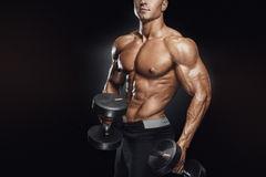 Handsome athletic guy workout with dumbbells Stock Photos