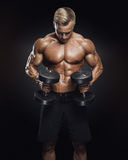 Handsome athletic guy workout with dumbbells