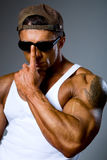 Handsome athletic man adjusts his sunglasses Stock Images