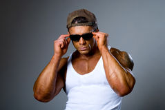 Handsome athletic man adjusts his sunglasses. Royalty Free Stock Photo