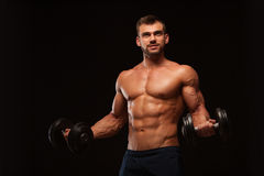 Handsome athletic man in gym is pumping up muscles with dumbbells in a gym. Fitness muscular body  on dark. Background Stock Photos