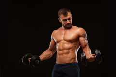 Handsome athletic man in gym is pumping up muscles with dumbbells in a gym. Fitness muscular body isolated on dark. Background Stock Photo