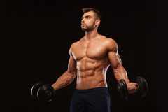 Handsome athletic man in gym is pumping up muscles with dumbbells in a gym. Fitness muscular body isolated on dark. Background Royalty Free Stock Photo
