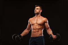 Handsome athletic man in gym is pumping up muscles with dumbbells in a gym. Fitness muscular body isolated on dark. Background Stock Photography