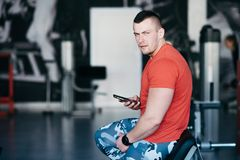 Handsome athletic man in gym, use mobile phone, surfing internet social network. Guy rest after exercise in fitness center. Male model with tattoo Stock Photography