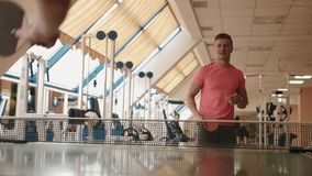 Handsome athletic man is playing table tennis or ping pong with unknown woman at modern gym. 4k footage. stock footage