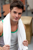 Handsome athletic man standing with a towel Royalty Free Stock Photography