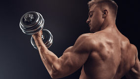Handsome athletic man working out with dumbbells. Closeup of a handsome power athletic man bodybuilder doing exercises with dumbbell. Fitness muscular body on Royalty Free Stock Images