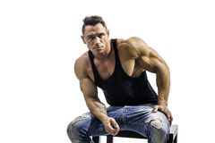 Handsome muscle man in black t-shirt. Handsome athletic muscle man in black t-shirt isolated on white, looking at camera, sitting on stool Stock Photos