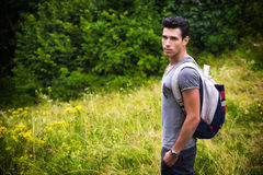 Handsome athletic young man with backpack in mount Stock Image
