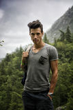Handsome athletic young man with backpack in mountains Stock Photo
