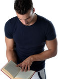 Handsome and athletic young man reading book Royalty Free Stock Photography