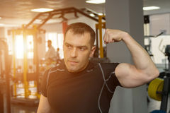Handsome athletic young man showing his biceps posing in gym. Sunlight Royalty Free Stock Images
