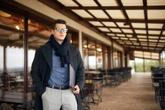 Handsome attractive businessman using a laptop on office terrace. Stylish man in glasses coat and scarf standing on. Handsome attractive businessman using a Royalty Free Stock Photography