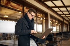 Handsome attractive businessman using a laptop on office terrace. Stylish man in glasses coat and scarf standing on. Handsome attractive businessman using a Royalty Free Stock Images