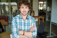 Handsome attractive cheerful young curly man with arms crossed Stock Photo