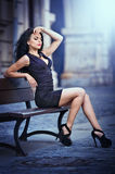 Handsome attractive girl wearing short skirt and high heels standing outside in urban scene. Fashion model in blue short skirt with long sexy legs on the street Stock Image