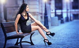 Handsome attractive girl wearing short skirt and high heels standing outside in urban scene Stock Images