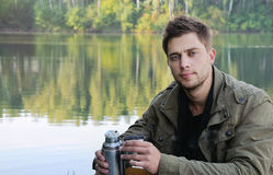 Handsome attractive man at the lake on beautiful nature backgrou Stock Image