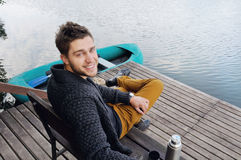 Handsome attractive man on the wooden pier at the lake, lifestyl Royalty Free Stock Images