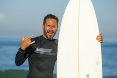 Handsome and attractive surfer man in neoprene swimsuit holding surf board posing cool after surfing enjoying Summer water sport royalty free stock image