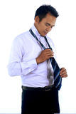 A handsome attractive young Asian businessman dressing,making tie. Photo image of a handsome attractive young Asian businessman dressing,making tie isolated on Stock Photo
