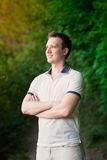 Handsome attractive young man standing in the park Stock Photos
